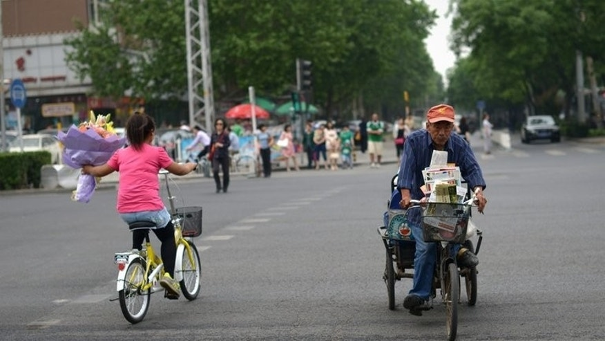 An elderly man (R) rides his tricycle across a road as a girl rides past holding flowers in Beijing on May 21, 2013. A Chinese law requiring family members to visit their elderly relatives went into effect Monday to howls of online ridicule, as the country's huge population ages rapidly.