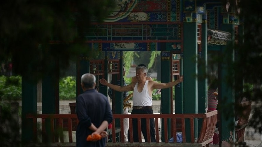 An elderly man (R) exercises in a pavilion at a park in Beijing on June 7, 2013. China's rapid development has challenged its traditional extended family unit, and reports of elderly people being neglected or mistreated by their children have shocked the country.