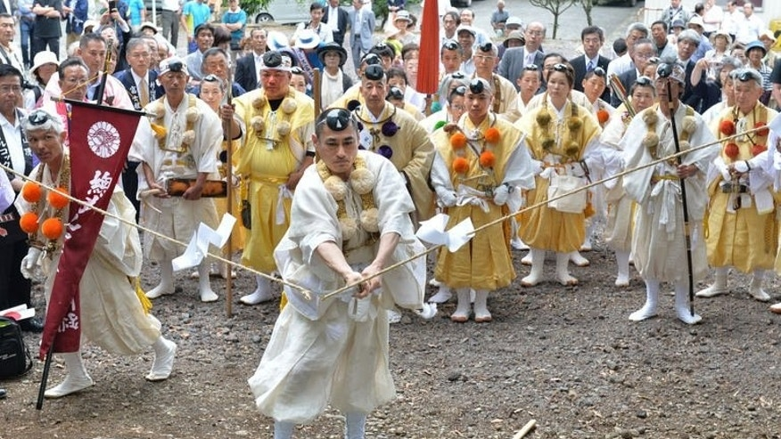 Yamabushi or Japanese Buddhist monks mark the official opening of Mount Fuji climbing season at Murayama Sengen Shrine in Fujinomiya, Shizuoka prefecture on July 1, 2013. Mount Fuji, Japan's national symbol newly inducted as a UNESCO World Heritage site, opened July 1 for a two-month-long climbing season.