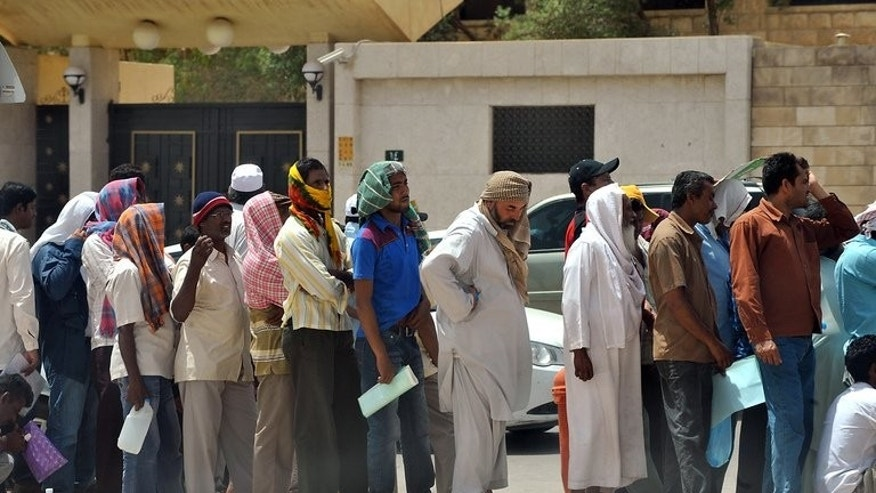 Foreign illegal labourers wait in a long queue outside immigration offices west of Riyadh on May 28, 2013. As in most Gulf states, foreigners in Saudi Arabia need to be sponsored by a local business to obtain entry and work permits.