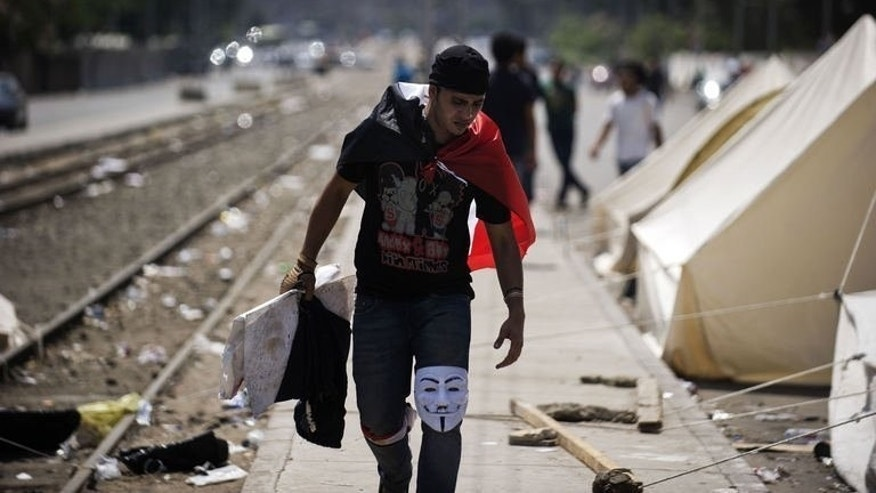 An Egyptian protester with a Guy Fawkes mask on his knee walks past tents set up by opposition supporters outside the presidential palace in Cairo on July 1, 2013.