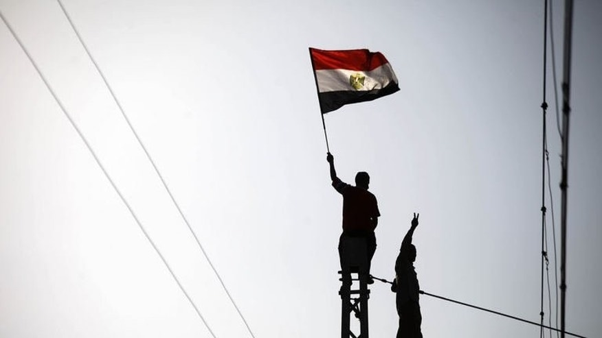 An Egyptian protester waves the national flag during a protest calling for the ouster of Islamist President Mohamed Morsi outside the presidential palace in Cairo on June 30, 2013.