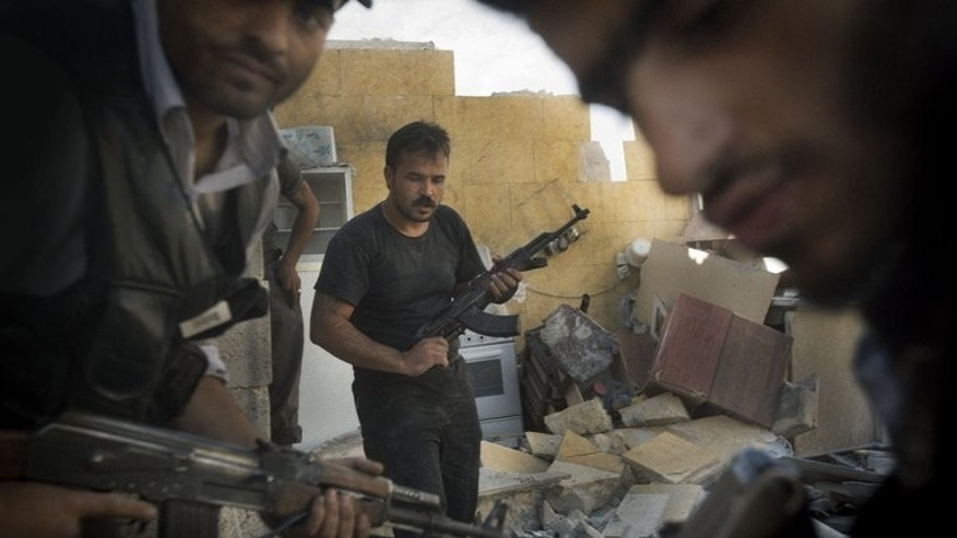 "Syrian opposition fighters pictured in the northern city of Aleppo on May 27, 2013. Arab states of the Gulf have urged the UN Security Council to hold an emergency meeting to prevent a ""massacre"" in Syria's central city of Homs, the target of a fierce offensive by regime troops."