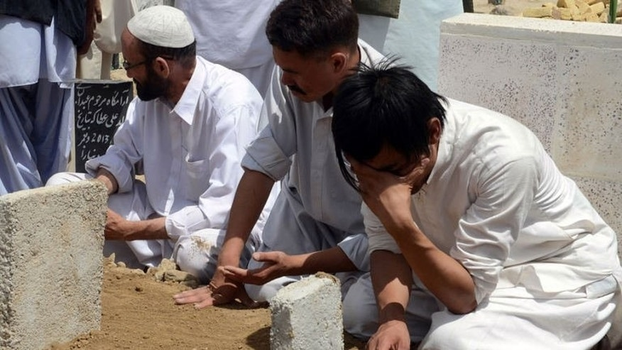Pakistani Shiite Muslim mourners sit around the graves of the victims of an overnight suicide bombing at a graveyard in Quetta on July 1, 2013. Gunmen ambushed a police checkpoint on Monday in Pakistan's troubled northwestern city of Peshawar, killing two policemen, an official said.