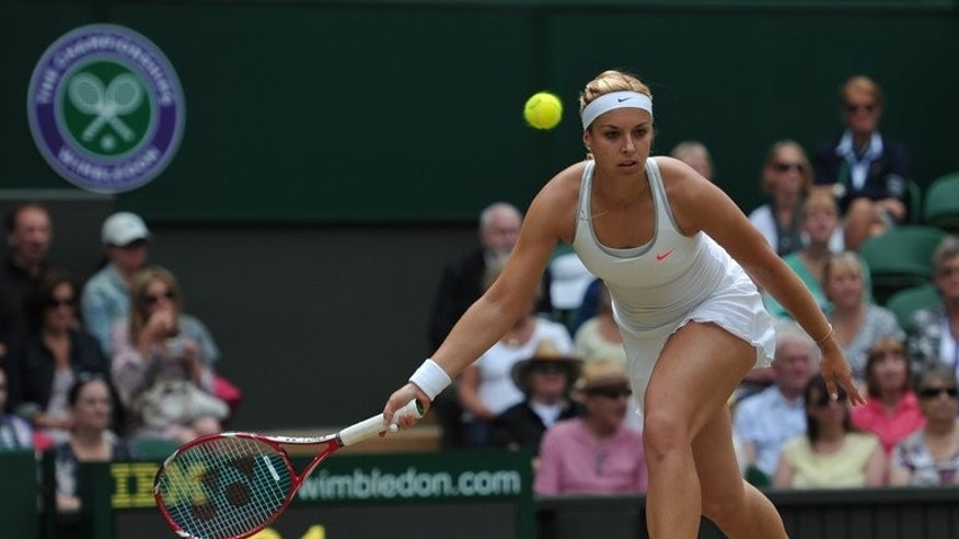 Sabine Lisicki hits to return against Serena Williams at Wimbledon on Monday. Despite facing the most ferocious hitter in the history of women's tennis, Lisicki matched Serena blow for blow, unloading more winners and serving more aces than the five-time Wimbledon champion in two hours and four minutes of high drama.