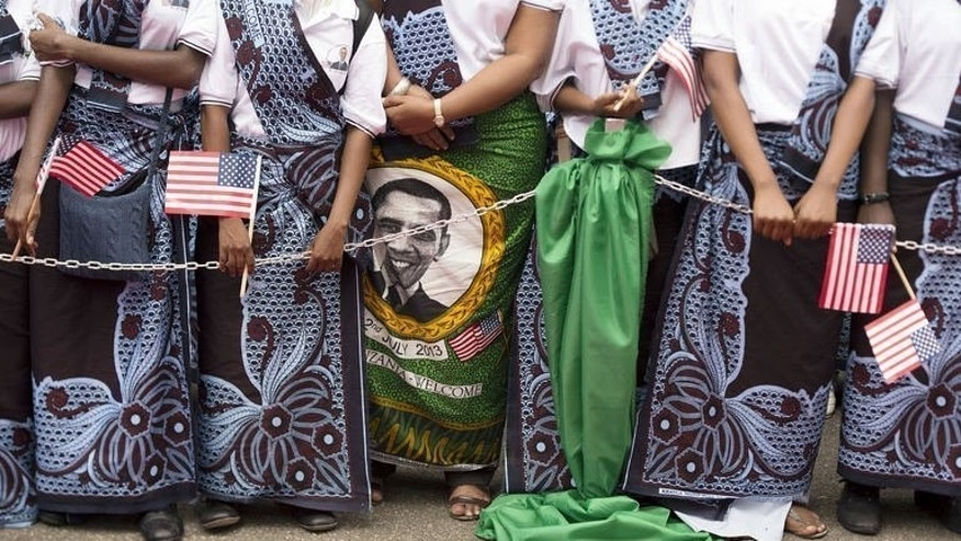 Women wearing traditional khanga wraps bearing a portrait of US President Barack Obama wait on July 1, 2013 outside State House in Dar es Salaam. Obama ends his Africa tour Tuesday, with an unusual double act with his predecessor George W. Bush, whose HIV/AIDS program saved millions of lives on the continent.