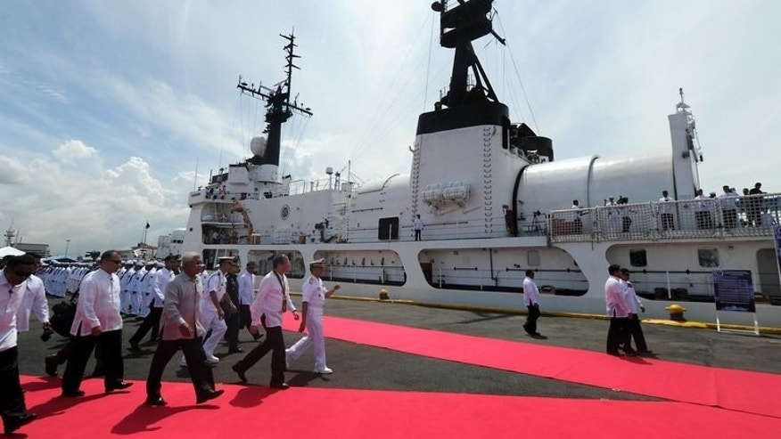 This file photo shows Philippine President Benigno Aquino and government officials arriving to inspect a warship, in Manila, on August 23, 2011. Aquino vowed on Monday to acquire fighter jets, air defence radar and other equipment within three years to bolster the country's weak air force, amid a territorial dispute with China.