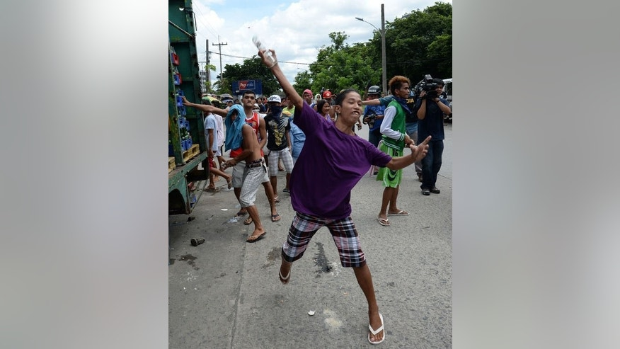 Philippine slum dwellers throw botltles at anti-riot policemen (not pictured) during clashes in Manila, on July 1, 2013. Slum dwellers hurled rocks, improvised explosives and human excrement fought running battles with riot police around a sprawling Manila shanty town that is set for redevelopment.