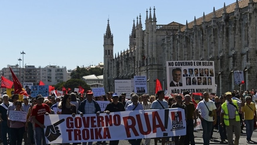 "Demonstrators hold a giant banner reading: ""Government, Troika out!"" during a protest against the government's austerity policies near Belem Presidential palace in Lisbon on May 25, 2013."