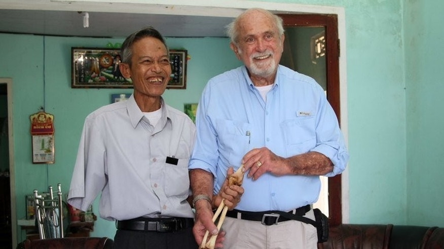 US veteran doctor Sam Axelrad (right) holds the preserved arm bone of ex-Viet Cong soldier Nguyen Quang Hung during a reunion in An Khe, on July 1, 2013. Axelrad said he had returned the carefully-preserved arm bone of a Viet Cong soldier to its owner more than forty years after he amputated it during the Vietnam War.