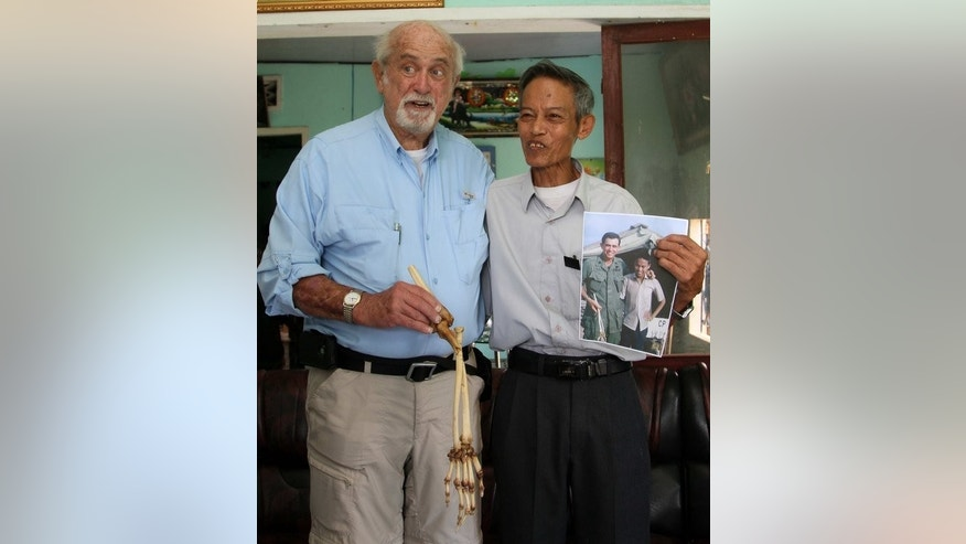 US doctor Sam Axelrad (left) holds the preserved arm bone of Nguyen Quang Hung, as the former Viet Cong soldier holds a photograph taken in 1966, during an emotional reunion in An Khe, on July 1, 2013. Axelrad said on July 1 he had returned the carefully-preserved arm bone of a Viet Cong soldier to its owner more than forty years after he amputated it during the Vietnam War.