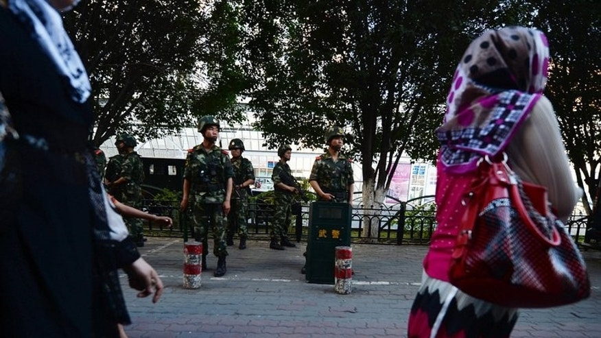 "A woman walks by Chinese paramilitary police in Urumqi, Xinjiang, on June 30, 2013. Western media are encouraging ""terrorism"" in Xinjiang by misrepresenting violence in the region as ethnic conflict between minority Uighurs and Han Chinese, state-run media said."