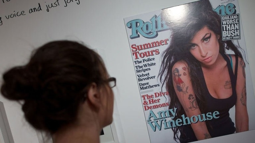 "A woman looks at a poster sized print of the cover of Rolling Stone magazine featuring a picture of British singer Amy Winehouse displayed at the ""Amy Winehouse A Family Portrait"" exhibition at the Jewish Museum in North London on July 2, 2013."