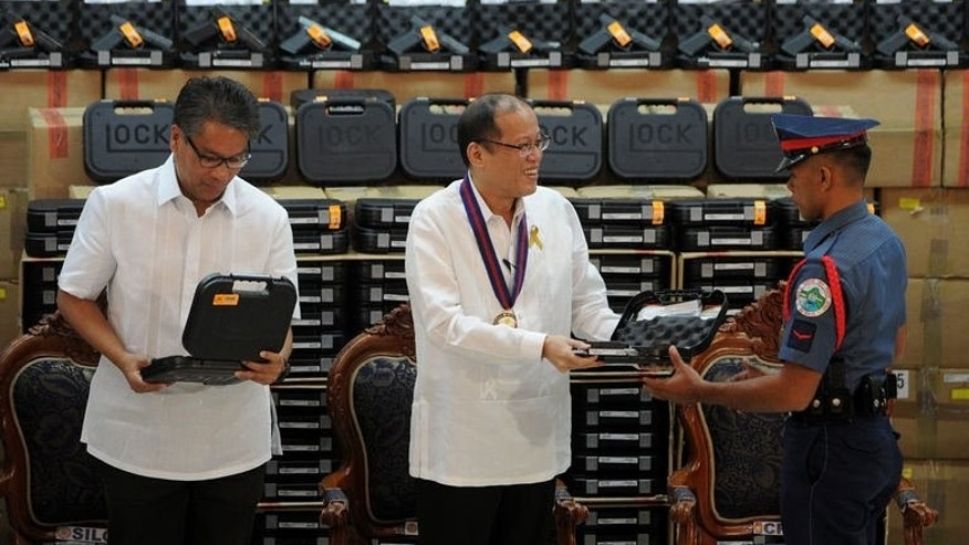 Philippine President Benigno Aquino (C) hands over a Glock 17 pistol to a police officer in Manila on July 2, 2013, as Interior and Local Government Secretary Mar Roxas (L) looks on. Aquino said Tuesday tens of thousands of police officers would finally get service pistols after having gone without guns for years because the government lacked the money to buy them.