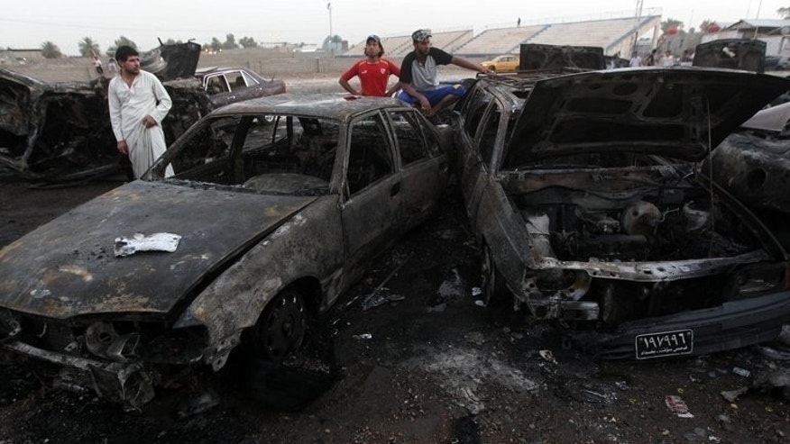 Iraqi men gather at the scene of a car bomb that exploded in Baghdad's Habibiyah area on May 27, 2013. A series of bombings minutes apart targeting markets across Baghdad have killed at least 15 people and wounded dozens of others, security and medical officials said.