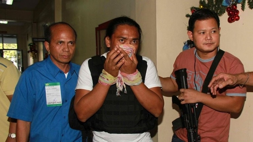 This photo, released by the Criminal Investigation and Detection Group (CIDG), shows Maguindanao Massacre suspect, Bong Andal (C), being escorted by CIDG operatives during his arrival at the Ninoy Aquino International Airport (NAIA) in Manila, on November 27, 2012.