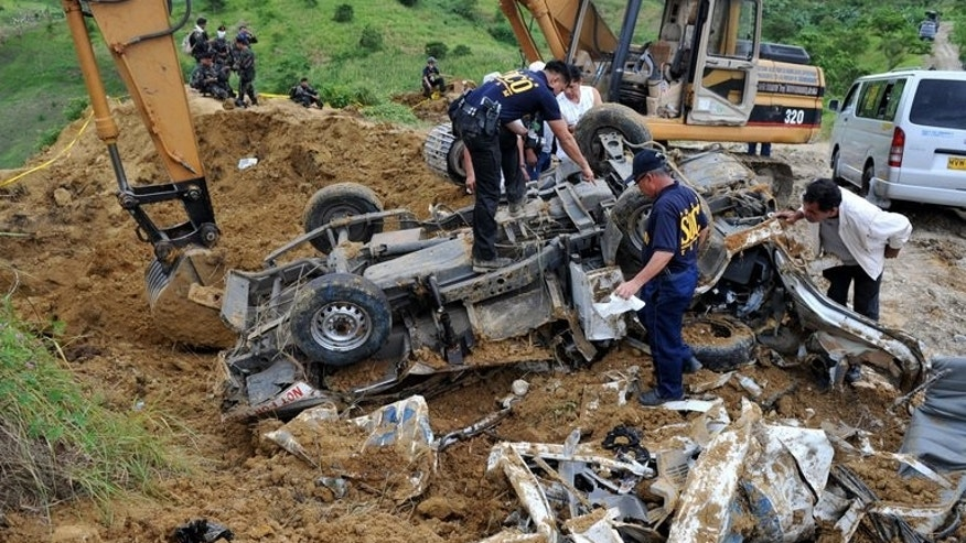 This file photo, taken on November 25, 2009, shows police investigators looking for evidence next to a backhoe, on a mangled vehicle unearthed at the crime scene where human remains were dug up from a shallow grave as investigators try to find more bodies, victims of a massacre after gunmen shot people in the town of Ampatuan, Maguindanao province in the southern Philippines.