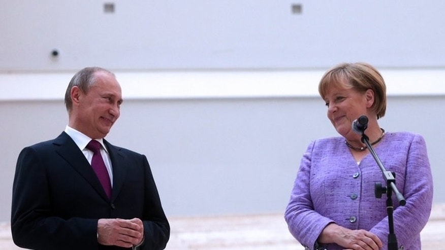 Russian President Vladimir Putin and German Chancellor Angela Merkel at the State Hermitage fine art museum in St. Petersburg on June 21, 2013.