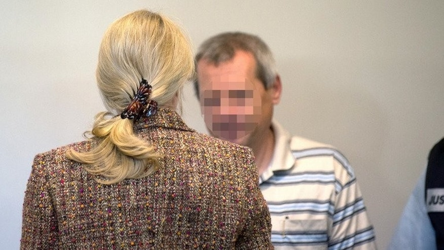 The woman codenamed Heidrun (front) and her husband Andreas Anschlag face each other at a regional court in Stuttgart, southern Germany, on July 2, 2013 on the last day of their trial for spying for the Russian secret services. A German court Tuesday jailed the couple for spying for Russia for more than 20 years in one of the country's biggest espionage cases since the Cold War.