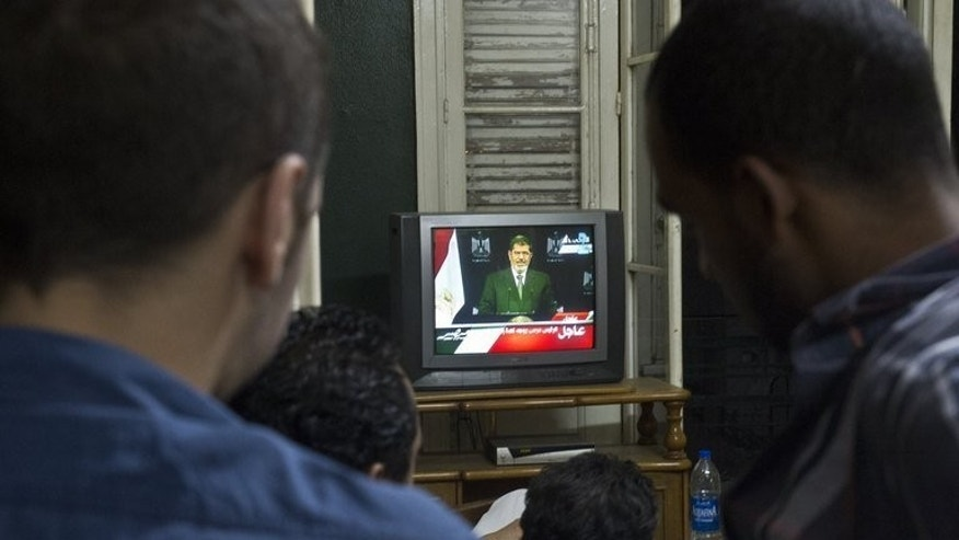 Egyptians in Cairo watch President Mohamed Morsi as he addresses the nation on television on July 2, 2013. Morsi warned that the only alternative to respecting the constitutional legitimacy of his presidency was further bloodshed on the streets.