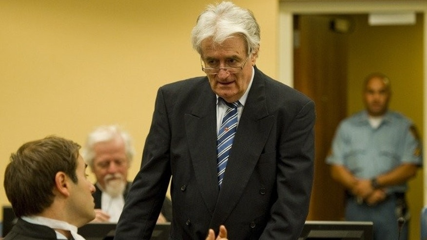 Former Bosnian Serb leader Radovan Karadzic talks to a member of his legal team on the first day of his defense against war crime charges at the International Criminal Tribunal for the Former Yugoslavia in The Hague, Netherlands on October 16, 2012. The tribunal, which saw some of its powers transferred to a new body in The Hague on Monday, has come under fire for a series of recent acquittals.