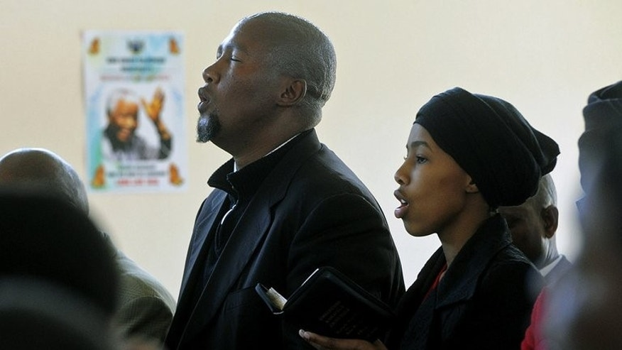 Mandla Mandela (L), grandson of former South African president Nelson Mandela, as well as his wife Nodiyala (R) and other family members pray during a service for Nelson Mandela on June 30, 2013 in Qunu. The Mandela family is seeking criminal charges of grave tampering against his Mandla Mandela, police said Tuesday.