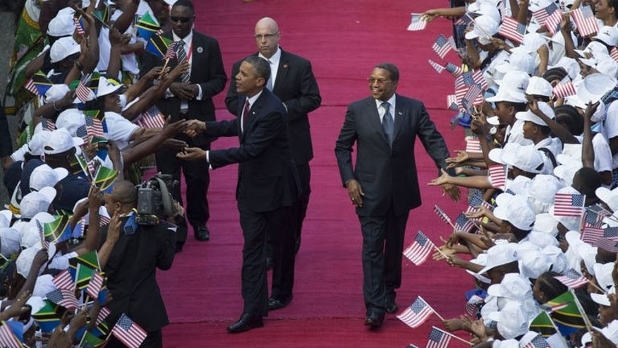 US President Barack Obama and Tanzanian President Jakaya Kikwete (R) are greeted by a cheering crowd as they arrive at the State House on July 1, 2013, in Dar es Salaam. It was billed as a new chapter in relations with a continent on the move, but Obama's whirlwind tour of Africa left many underwhelmed by pledges that were thin on detail and dwarfed by China's lavish investment.