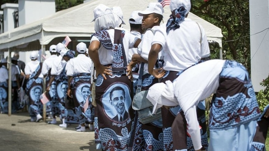 Women, wearing khanga traditional wraps with portraits of US President Barack Obama, wait on July 1, 2013 in Dar es Salaam. Obama vowed not to dole out cash gifts as he touted US-style investment and partnership as superior to Beijing's Africa push, arguing US companies do more to build local economic capacity.