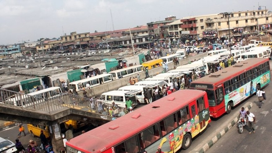 Buses are seen near a market in Lagos on February 1, 2012. Long queues have formed at petrol stations in some Nigerian cities after a key oil workers union ordered a three-day strike to demand better conditions and road repairs.