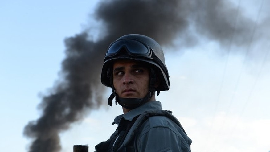 "An Afghan policeman guards the site of a suicide attack in Kabul on July 2, 2013. Pakistan could end the Afghan war ""in weeks"" if it were serious about peace, and is complicit in US drone strikes despite its denunciations of the anti-militant campaign, Afghanistan's army chief says."
