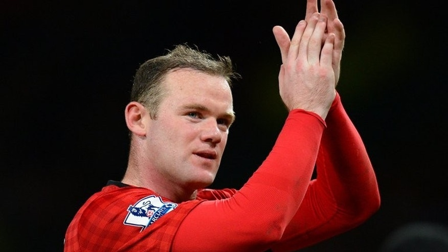 "Manchester United's Wayne Rooney acknowledges the crowd after the final whistle in the league match against Everton at Old Trafford, on February 10, 2013. Rooney may wish to leave the Premier League champions in order to seek a ""fresh challenge"" elsewhere, according to former assistant coach Mike Phelan."