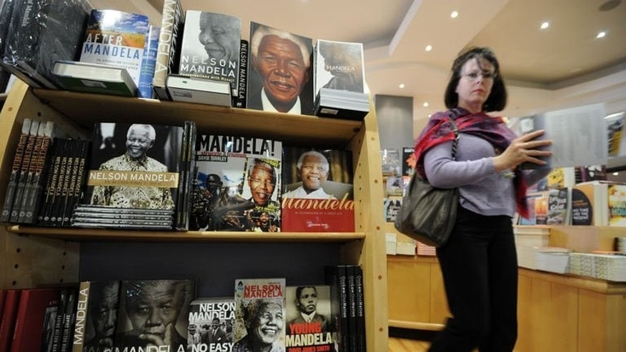 "Books on former South African President Nelson Mandela displayed in a book shop in Johannesburg, on June 30, 2013. Mandela's prolonged illness has sparked intense interest in the anti-apartheid icon's life and times with books, shirts and other ""Madiba merchandise"" flying off the shelves."
