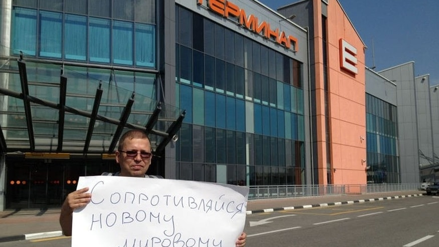 A supporter of National Security Agency (NSA) leaker Edward Snowden holds a poster outside Sheremetyevo airport, in Moscow, on June 28, 2013. The poster reads : Fight against new world order !