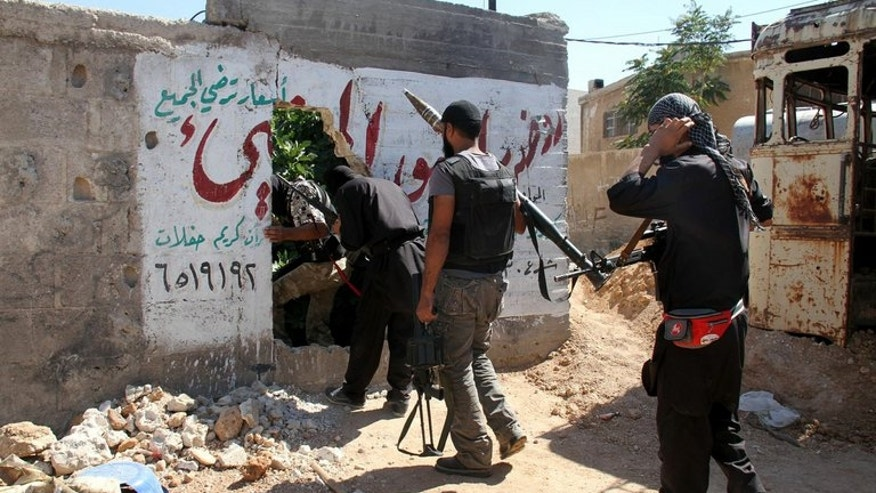 A handout picture released by the opposition-run Shaam News Network on June 22, 2013 shows rebel fighters walking through a hole in a wall as they carry their weapons in the Syrian capital Damascus. At least 14 people have been killed in army shelling on a rebel village near Damascus as violence raged in the central city of Homs, according to the Syrian Observatory for Human Rights.