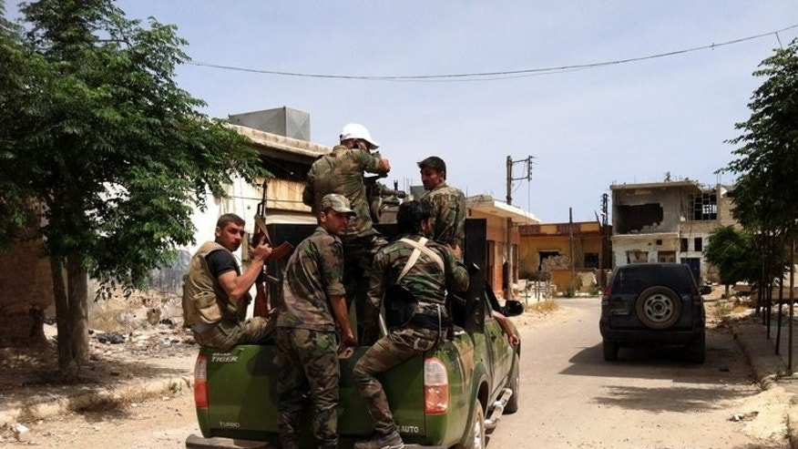 Syrian soldiers patrol a street in the village of Buweida, in central Homs province, on June 8, 2013. At least 14 people have been killed in army shelling on a rebel village near the Syrian capital as violence raged in flashpoint areas of Damascus and in the central city of Homs, according to the Syrian Observatory for Human Rights.