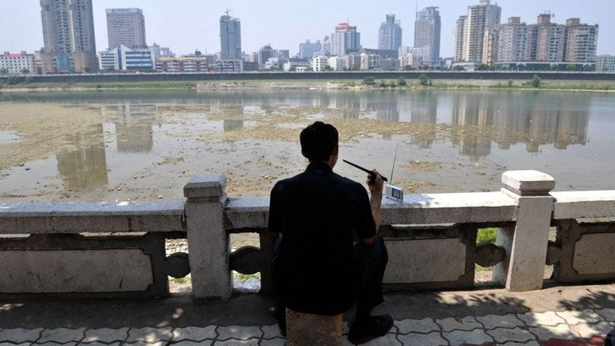 A man eats a meal as he listens to the radio in front of the Fujiang river in China's southwestern province of Sichuan on June 3, 2008. Several US legislators have urged Taiwan to stop tearing down shortwave radio transmission towers which have broadcast uncensored news to China since the 1960s.