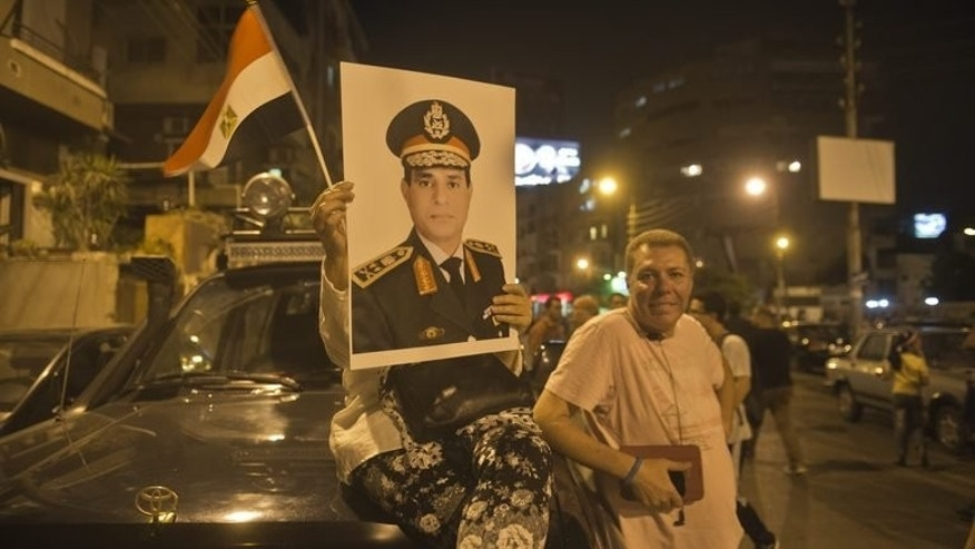An Egyptian protester carries a portrait of army chief General Abdel Fattah al-Sisi outside the presidential palace in Cairo on July 1, 2013. Sisi, who is emerging as Egypt's strongman amid the turmoil sweeping the country, is desperate to end the crisis but without a return to the unpopular military rule of 2011-2012, experts say.