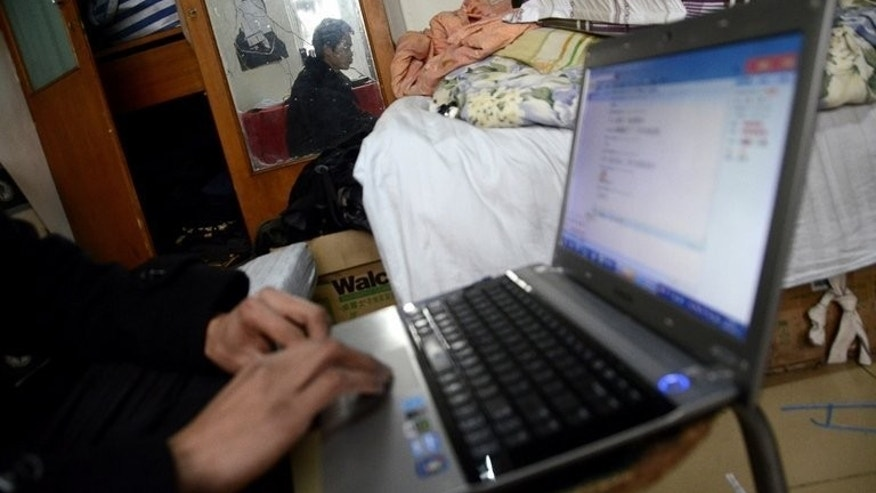 File picture shows a man using a social networking site on his laptop, January 31, 2013. The British couple who sold social networking site Bebo for $850 million (655 million euros) five years ago have bought back the company for just $1 million and say they will relaunch it.