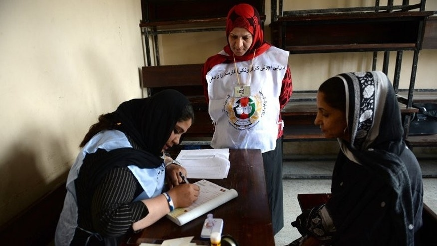 An Afghan woman (right) is assisted by an election official as she gives details to obtain her voter registration card in Kabul on May 26, 2013. Donor nations funding Afghanistan's recovery piled pressure Wednesday on the government to pass election laws seen as crucial to proving the 12-year war and billions of dollars of aid money have not been wasted.