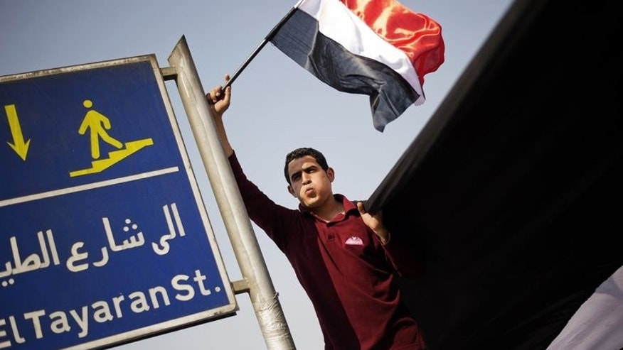 An Egyptian protester waves the national flag outside the Ministry of Defense in Cairo on July 3, 2013. An army deadline to Egypt President Mohamed Morsi to meet the demands of his people or face army intervention expired on Wednesday at 4:30 pm (1430 GMT).