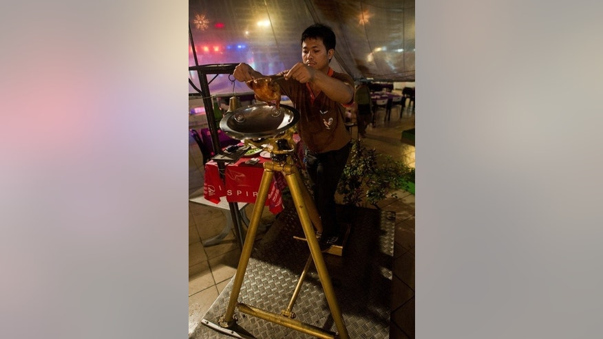 """A waiter puts a cooked chicken into a catapult at Ka Tron restaurant in Bangkok on June 19, 2013. """"We have been going 26 years and we have probably fired hundreds of thousands of chickens, but we have only dropped a few hundred,"""" said the restaurant owner."""