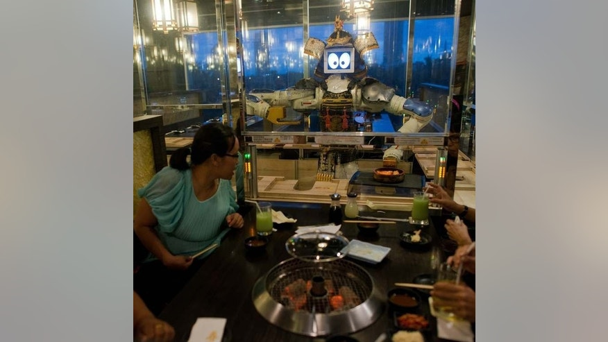 Costumers are being served by a robot at the Hajime restaurant in Bangkok on June 19, 2013. Two large robots wheel up and down the tables delivering meals to diners.