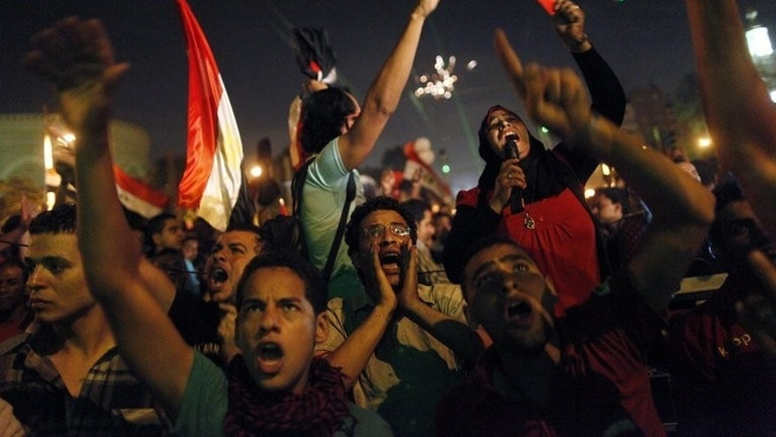 Egyptian protesters calling for the ouster of President Mohamed Morsi react as they watch his speech on a screen near the presidential palace in Cairo on July 3, 2013.