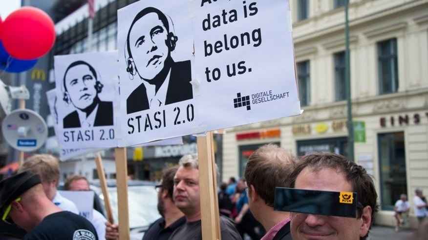 "Protestors hold posters reading ""Stasi 2.0"" depicting US President Barack Obama wearing headphones, on June 18, 2013 in Berlin. France is calling for the temporary suspension of talks on a huge EU-US free trade pact after allegations of widespread US spying on European offices, the government's spokeswoman said on Wednesday."