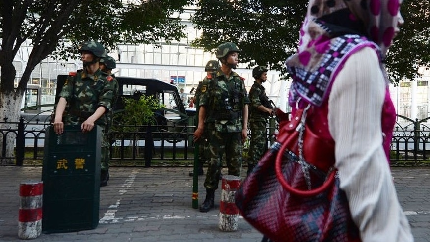 Chinese paramilitary police stand guard in the Muslim Uighur minority area of Urumqi, Xinjiang Province on June 30, 2013. Beijing's propaganda portrays the vast and remote western region of Xinjiang as a harmonious land of colourful, mostly Muslim Uighur natives and hard-working migrants prospering under Communist Party rule.