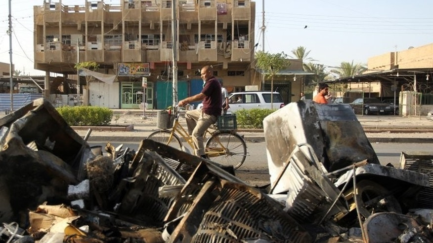 A man cycles past the aftermath of a car bomb attack on July 3, 2013 following an explosion the previous day at a convenience store in the northern Baghdad neighbourhood of Shaab. A bombing on Baghdad's southern outskirts killed seven people Wednesday, the latest in a three-day wave of bloodshed targeting Shiite Muslims that has left 113 dead.