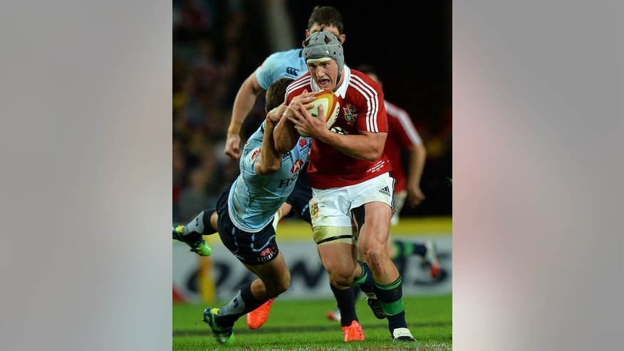 Jonathan Davies of the British and Irish Lions is tackled by Waratahs players during their match in Sydney on June 15, 2013. Davies and teammate Jamie Roberts will have to find gaps in the Aussie defence to steer the Lions to a series win.