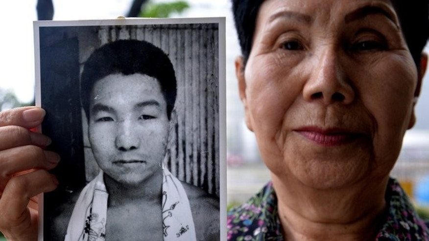 Hideko Hakamada, sister of death-row prisoner Iwao Hakamada, holds a picture of her brother, outside Tokyo Detention House, on May 20, 2013. The former boxer has been behind bars since 1966.