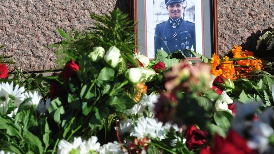 Flowers and a photo of a soldier wearing a uniform with Gestapo insignia and the Iron Cross are laid at the Monument of Freedom in Riga, Latvia where veterans of a force that was commanded by the German Nazi Waffen SS commemorated a key 1944 battle on March 16, 2013. The Simon Wiesenthal Centre Wednesday condemned plans by Latvian nationalists to mark a WWII event that led to a massacre of Jews.