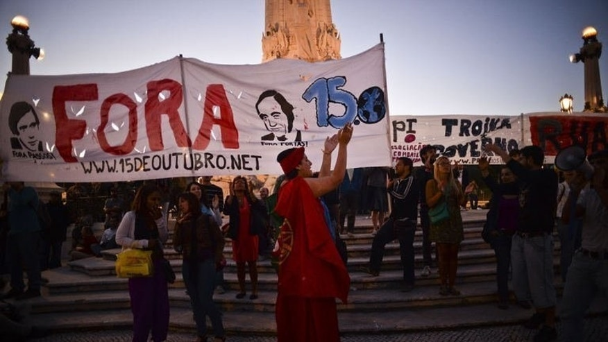 "Protesters gather at the Marques de Pombal Statue holding a banner reading ""Out"" during an anti-government protest in Lisbon, on July 2, 2013. Portuguese Prime Minister Pedro Passos Coelho's government is tottering close to collapse after two top ministers quit, pounding financial markets in Lisbon and across Europe."